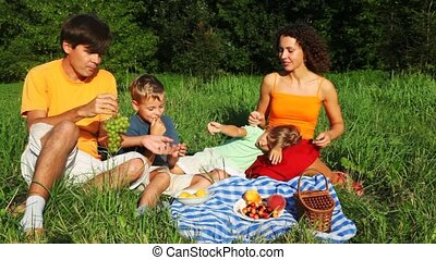 family with daughter and son sits on lawn and eats fruit, vine and cherry