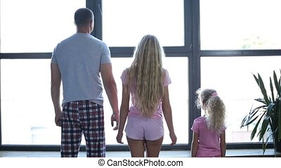 Family with daughter holding hands by the window - Positive...