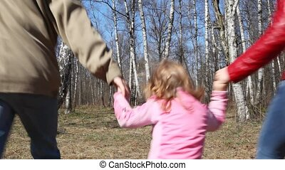 family with daughter runs from camera to forest