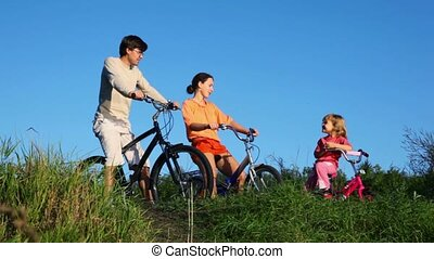 family with daughter sits on bicycles and talks