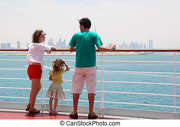 family with daughter standing on cruise liner deck, view from back, city on horizon