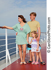 family with daughter standing on cruise liner deck, full body, looking left