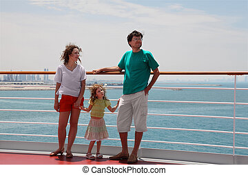 family with daughter standing on cruise liner deck and looking right, city on horizon