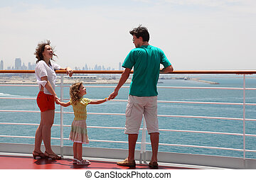 family with daughter standing on cruise liner deck and holding for hands, city on horizon