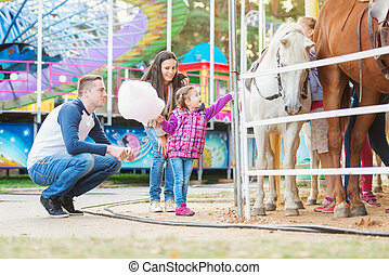 Family with daughter stroking pony in amusement park -...