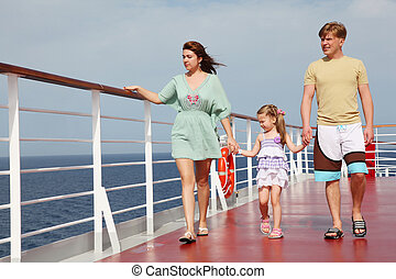 family with daughter walking on cruise liner deck, full...