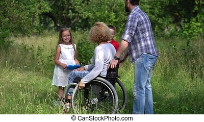 Family with disabled mother outdoors.