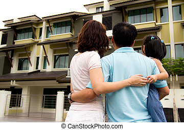 Family with dream house - Couple with a kid in front of a...