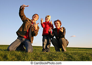 family with fingers on grass