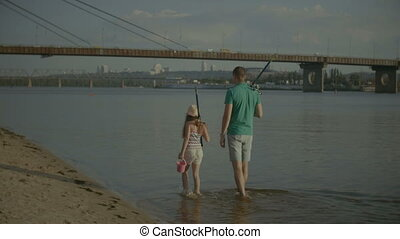 Family with fishing rods walking along riverbank - Rear view...