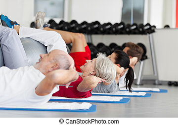 Family With Fitness Ball Practicing Crunches In Gym - Side...