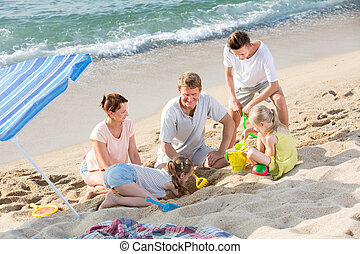 Family with four children playing on beach