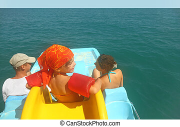 family with girl on pedal boat with yellow slide in sea, view from back on horizon, waterproof case