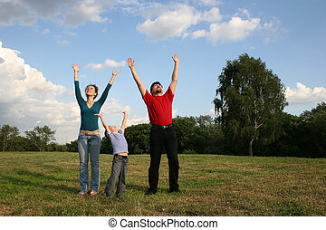 family with hands up on meadow
