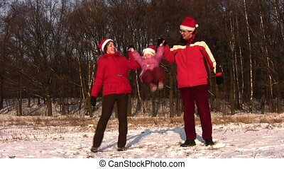 family with jumping little girl with christmas hats