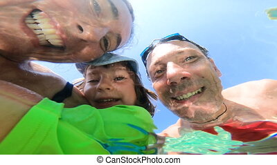 Family with kid having fun at the sea. Distorted faces view through water, underwater view