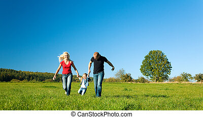 Family with kid on meadow in summer