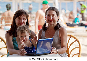 family with laptop at beach