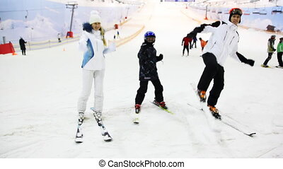 family with little boy show martial arts on ski in snow
