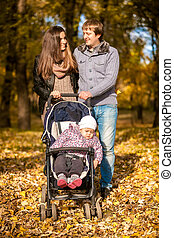 Family with little daughter in pram at autumn