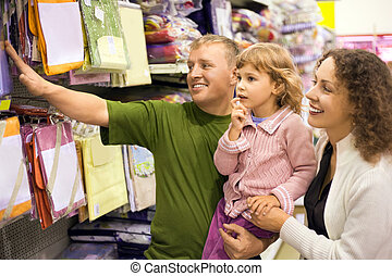 family with little girl buy bedding in supermarket