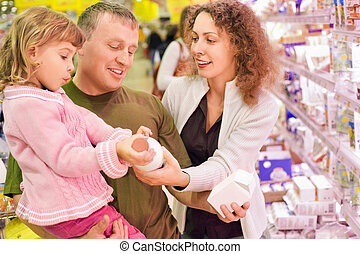 family with little girl buy milk in supermarket