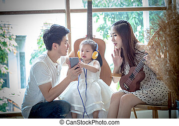 Family with little girl in Listen to music on your phone.