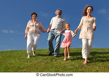 family with little girl, mother and grandparents holding for hands and walking on lawn