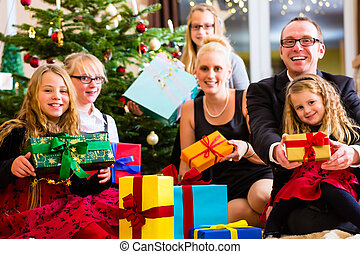 Family with lots of Christmas presents under tree