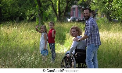 Family with mother in sheel chair look back and wave on camera.