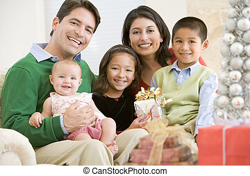 Family With New Born,Sitting On Sofa,Holding Christmas Gift