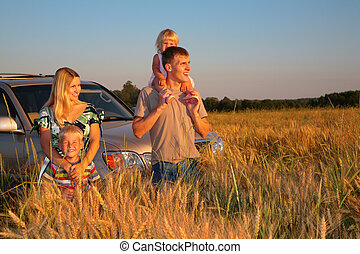 Family with offroad car on wheat field