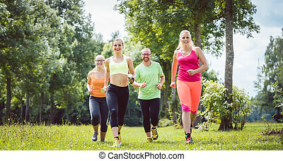 Family with personal Fitness Trainer jogging