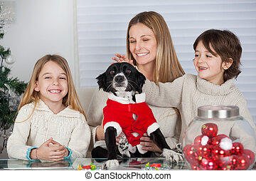 Family With Pet Dog At Home During Christmas