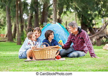 Family With Picnic Basket At Campsite