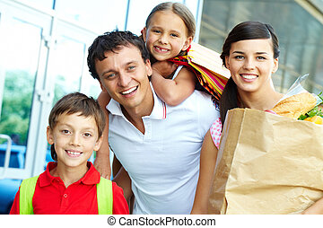Family with products - Couple with paperbags and their two...