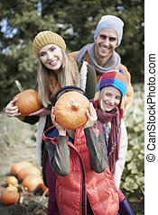 Family with pumpkins in autumn day