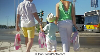 Family with shopping bags crossing the road