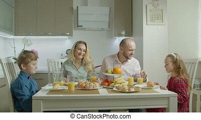 Family with siblings enjoying breakfast in kitchen - ...