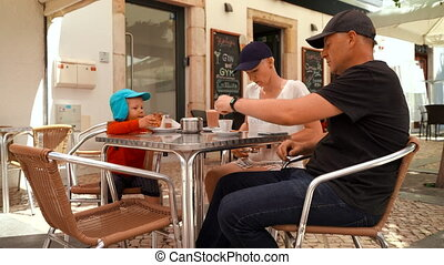 Family with small boy drinking and talking in cafe in Lagos, Portugal