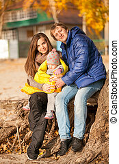 Family with small daughter sitting under tree