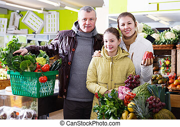 Family with small girl standing with full grocery cart in fruit shop
