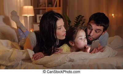 family with smartphone in bed at night at home