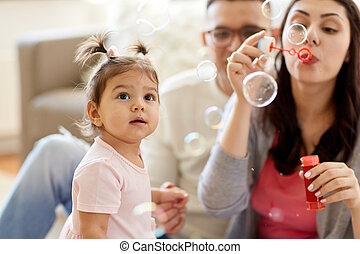 family with soap bubbles playing at home