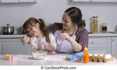 Joyful carefree mother and cute special needs daughter in matching aprons preparing dough for baking, having fun, arms and faces stained with flour. Cooking family stained with flour making batter.