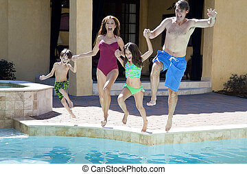 Family With Two Children Having Fun Jumping Into Swimming Pool