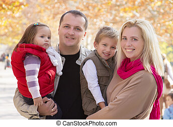 Family with two children in autumn park
