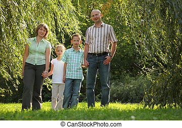 family with two children in early fall park. they are looking at camera.