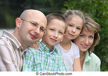 family with two children in early fall park near pond. focus on little boy\'s face.