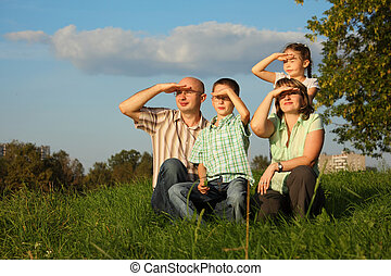 family with two children in early fall park. they sitting on grass and looking at sunset